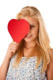 Schöne junge Blondine mit den blauen Augen, die rotes Hirschverbot halten Stockfoto
