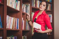 Schöne junge braunhaarige Frau in Bürokleidung stehendem nea lizenzfreie stockbilder