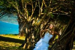 Schöne junge Braut, die auf tropischem Baumhintergrund aufwirft stockfoto