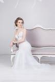 Schöne junge Braut in einem luxuriösen Spitzehochzeitskleid Sie sitzt auf einem weißen Weinlesesofa Stockfotos