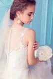 Schöne junge Braut mit dem dunklen gelockten Haar im luxuriösen Hochzeitskleid, das am Raum aufwirft lizenzfreies stockbild