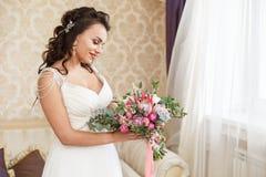 Schöne junge Braut mit den dunklen Haaren in einem Schlafzimmer stockfoto