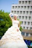 Schöne junge Braut mit einem Blumenstrauß auf der Natur Stockfotografie