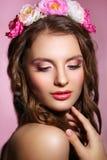 Schöne junge Braut mit einer Blumenverzierung in ihrem Haar Schöne Frau, die ihr Gesicht berührt Nacktes Make-up Stockfoto