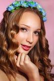 Schöne junge Braut mit einer Blumenverzierung in ihrem Haar Schöne Frau, die ihr Gesicht berührt Nacktes Make-up Stockbild