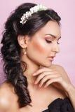 Schöne junge Braut mit einer Blumenverzierung in ihrem Haar Schöne Frau, die ihr Gesicht berührt Nacktes Make-up nymphe Stockfoto