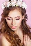 Schöne junge Braut mit einer Blumenverzierung in ihrem Haar Schöne Frau, die ihr Gesicht berührt Nacktes Make-up nymphe Stockfotos