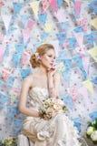 Schöne junge Braut mit Hochzeitsmake-up und -frisur im Schlafzimmer stockfoto