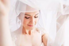 Schöne junge Braut mit Hochzeitsmake-up und -frisur im Schlafzimmer Schönes Brautporträt mit Schleier über ihrem Gesicht nahaufna lizenzfreies stockbild