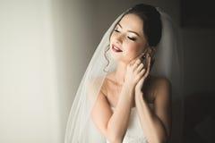 Schöne junge Braut mit Make-up und Frisur im Schlafzimmer, abschließende Vorbereitung der Jungvermähltenfrau für die Heirat Glück lizenzfreies stockfoto