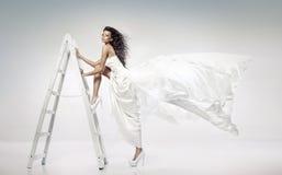 Schöne junge Braut, welche die Leiter hält stockfoto