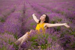 Schöne junge brunette Frau im gelben Kleid, das auf purpurrotem Blume lavander Gebiet sitzt Lachende glückliche freie Frau stockfoto