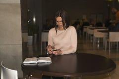 Schöne junge Brunettefrau, die an einem runden Holztisch sitzt Lizenzfreie Stockfotos