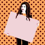 Schöne junge Brunettefrau, die einen freien Raum hält Lizenzfreies Stockfoto