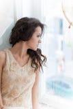 Schöne junge Brunettefrau, die heraus das Fenster schaut Stockbild