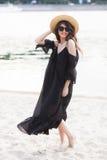 Schöne junge Brunettefrau im schwarzen Kleid, in der schwarzen Sonnenbrille und im Strohhut gehend auf den Sand auf dem Strand un Stockfoto