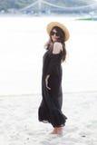 Schöne junge Brunettefrau im schwarzen Kleid, in der schwarzen Sonnenbrille und im Strohhut gehend auf den Sand auf dem Strand un Lizenzfreies Stockbild