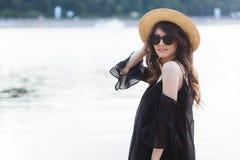 Schöne junge Brunettefrau im schwarzen Kleid, in der schwarzen Sonnenbrille und im Strohhut gehend auf den Sand auf dem Strand un Lizenzfreie Stockfotografie