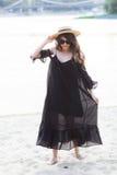 Schöne junge Brunettefrau im schwarzen Kleid, in der schwarzen Sonnenbrille und im Strohhut gehend auf den Sand auf dem Strand un Lizenzfreie Stockfotos