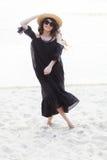 Schöne junge Brunettefrau im schwarzen Kleid, in der schwarzen Sonnenbrille und im Strohhut gehend auf den Sand auf dem Strand un Lizenzfreies Stockfoto