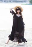 Schöne junge Brunettefrau im schwarzen Kleid, in der schwarzen Sonnenbrille und im Strohhut gehend auf den Sand auf dem Strand un Stockfotos