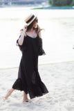 Schöne junge Brunettefrau im schwarzen Kleid, in der schwarzen Sonnenbrille und im Strohhut gehend auf den Sand auf dem Strand un Stockbild