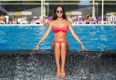 Schöne junge Brunettefrau mit dem langen Haar im rosa Bikini sitzen Stockfotos