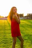 Schöne junge Brunettefrau mit dem langen Haar im roten Kleiderstand Stockfoto