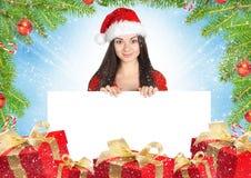 Schöne junge Brunettefrau mit weißer Karte, Geschenke buntes b lizenzfreie stockbilder