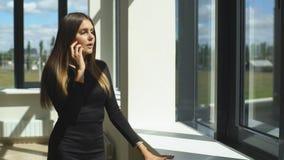 Schöne junge Brunettegeschäftsfrau, die am Telefon am Fenster spricht stock footage