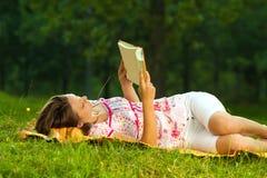 Schöne junge Brunettelesung auf einer Wiese im Park Lizenzfreie Stockfotos