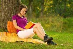 Schöne junge Brunettelesung im Park Stockbilder