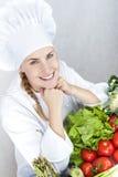 Schöne junge Cheffrau bereiten sich vor und geschmackvolles Lebensmittel herein verzierend Lizenzfreie Stockfotografie