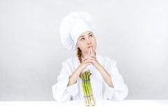 Schöne junge Cheffrau bereiten sich vor und geschmackvolles Lebensmittel herein verzierend Stockfotos