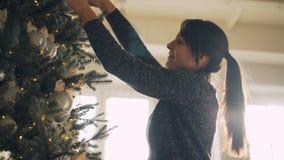 Schöne junge Dame in der Strickjacke verziert Baum des neuen Jahres mit dem stilvollen Dekorationsball- und -lichthängen stock footage