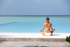 Schöne junge Dame, die auf einem Strand Malediven meditiert Lizenzfreie Stockfotos