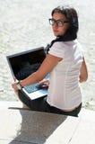 Schöne junge Dame, die auf Treppen mit Laptop sitzt Lizenzfreie Stockfotos