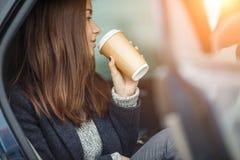 Schöne junge Dame, die im Auto und in trinkendem Kaffee sitzt Lizenzfreies Stockfoto