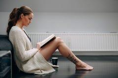 Schöne junge Dame, die zu Hause einen Roman liest stockfotos