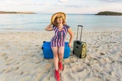 Schöne junge Dame mit einem blauen Koffer auf dem Strand Leute-, Reise-, Ferien- und Sommerkonzept Stockfoto