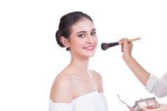 Schöne junge Dame mit hellem Make-up und Bürsten auf weißem Ba Lizenzfreie Stockfotografie