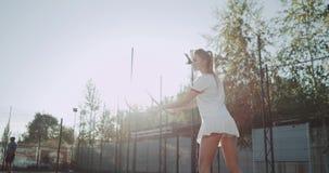 Schöne junge Dame mit langen sportiv Beinen, die Tennis auf dem Tennisplatz draußen am sonnigen Tag spielen stock video footage