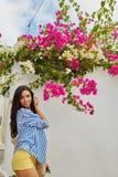 Schöne junge Dame nahe einer bouganvillea Blume lizenzfreie stockfotografie
