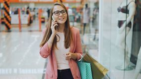 Schöne junge Dame spricht am Handy gehend in das Einkaufszentrum allein, das Papiertüten trägt Neue Kleidung an stock video