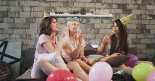 Schöne junge Damen, die zu Hause im Schlafzimmer den Geburtstag von jemand s, sehr glücklich sie trinkender Champagner feiern stock video footage