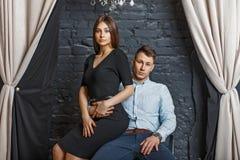 Schöne junge elegante Paare im stilvollen Kleidungssitzen lizenzfreies stockbild