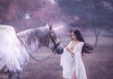Schöne, junge Elfe, gehend mit einem Einhorn Sie trägt ein unglaubliches Licht, weißes Kleid Kunst hotography lizenzfreies stockfoto