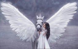 Schöne, junge Elfe, gehend mit einem Einhorn Sie trägt ein unglaubliches Licht, weißes Kleid Kunst hotography stockfoto