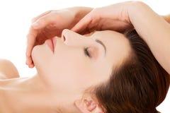 Schöne junge entspannte Frau genießen, Gesichtsmassage an SP zu empfangen lizenzfreie stockfotos
