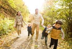 Schöne junge Familie auf einem Weg im Herbstwald Lizenzfreie Stockfotos